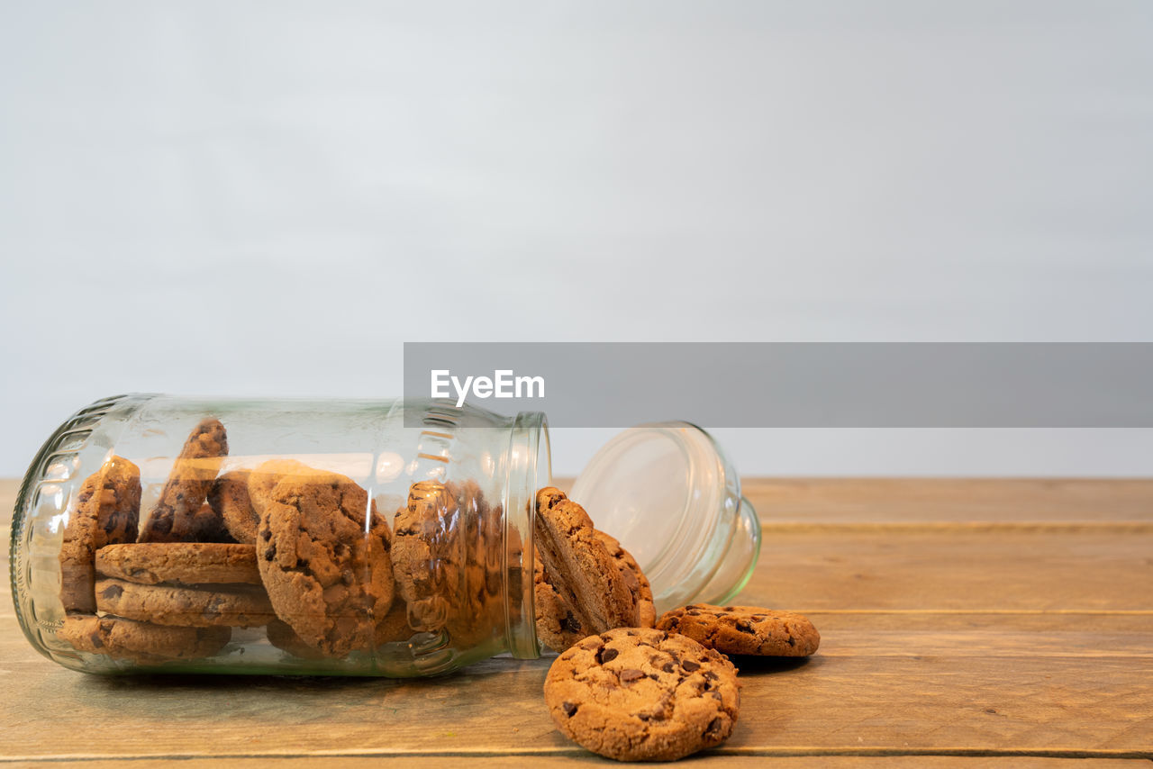 food and drink, food, still life, baked, cookie, table, freshness, sweet food, indulgence, indoors, temptation, wood - material, no people, close-up, ready-to-eat, cork - stopper, unhealthy eating, container, copy space, chocolate, snack, chocolate chip cookie