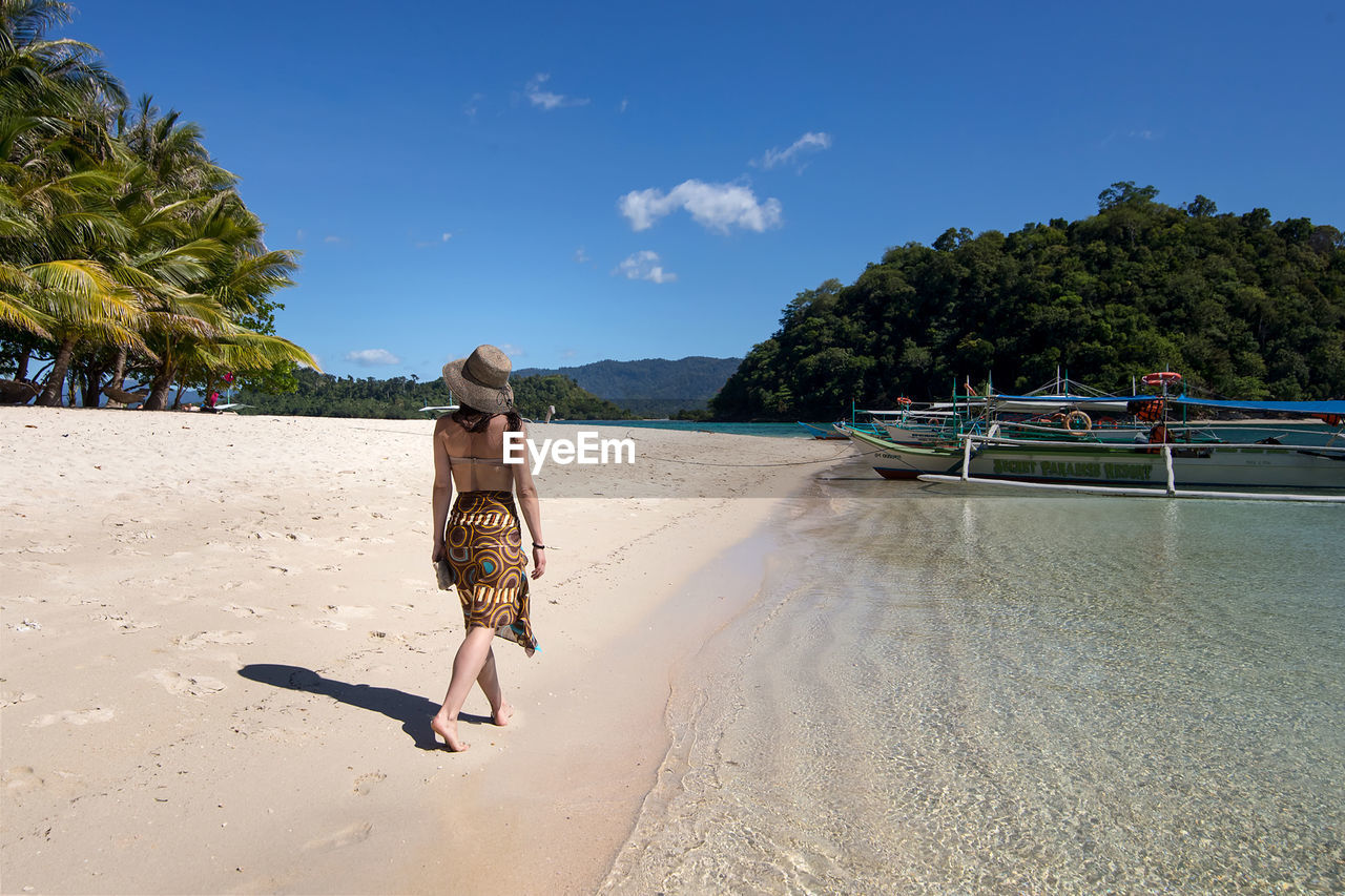 beach, land, water, sand, tree, sea, real people, sky, beauty in nature, one person, full length, nature, plant, scenics - nature, leisure activity, women, day, sunlight, lifestyles, outdoors