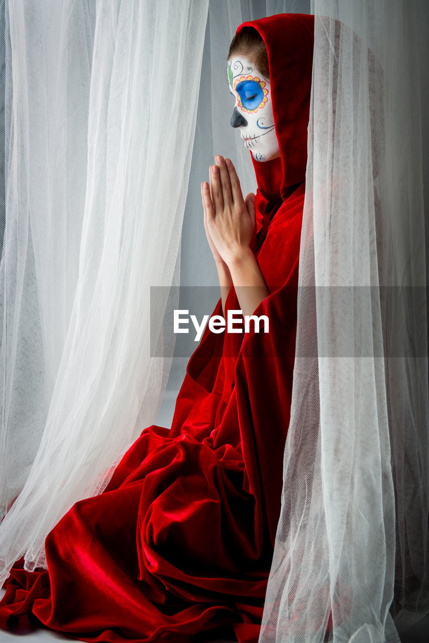 Woman With Halloween Make-Up Praying While Sitting Amidst Curtains