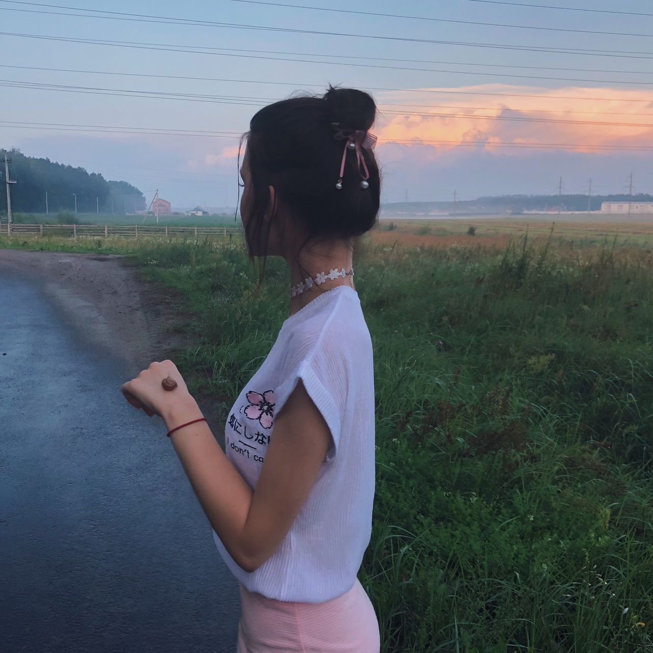 one person, real people, field, land, lifestyles, sky, standing, plant, leisure activity, casual clothing, nature, grass, landscape, environment, sunset, three quarter length, rear view, non-urban scene, waist up, outdoors, hairstyle