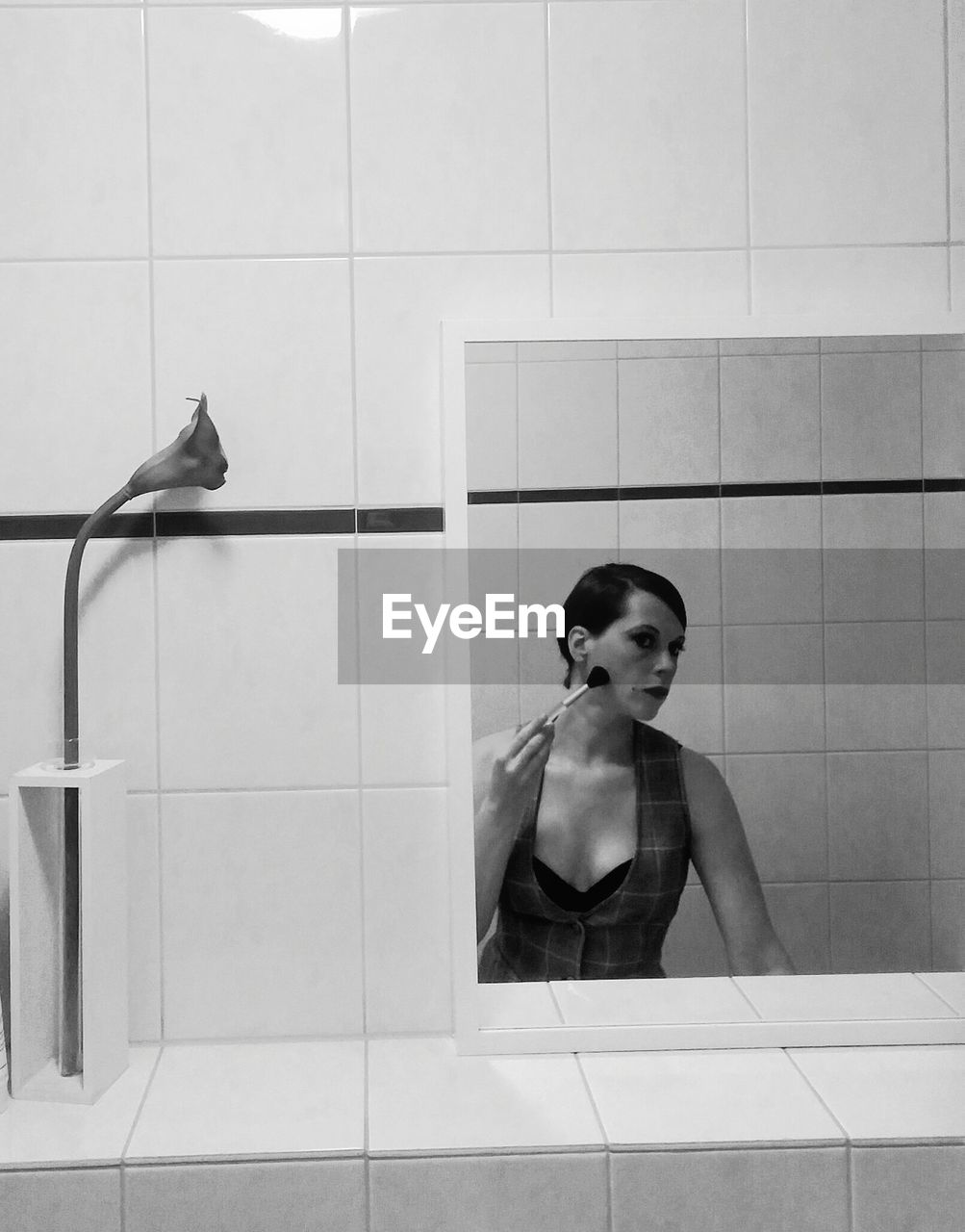 Reflection Of Woman Applying Make-Up On Mirror
