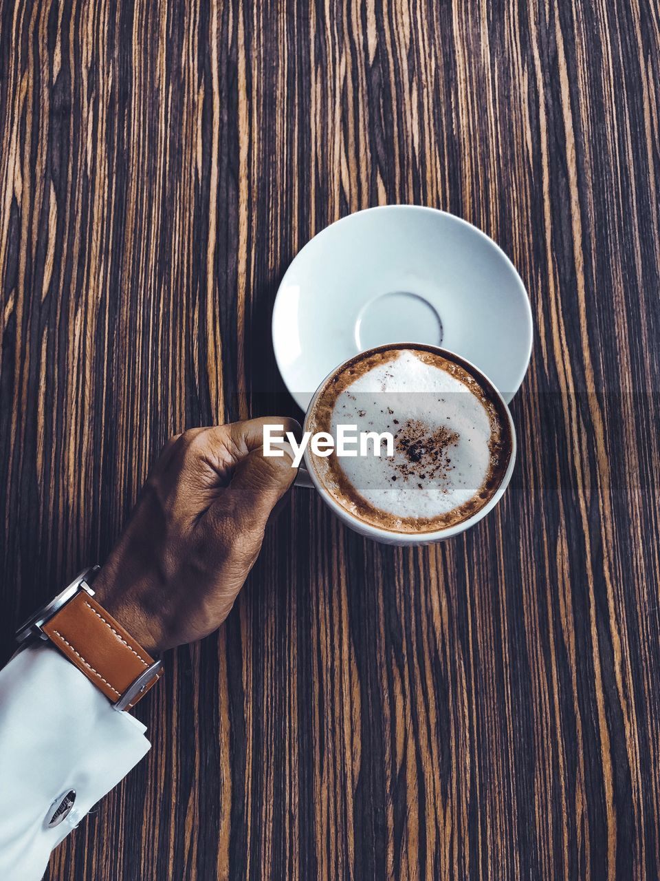 Cropped Hand Of Man Holding Coffee Cup On Wooden Table
