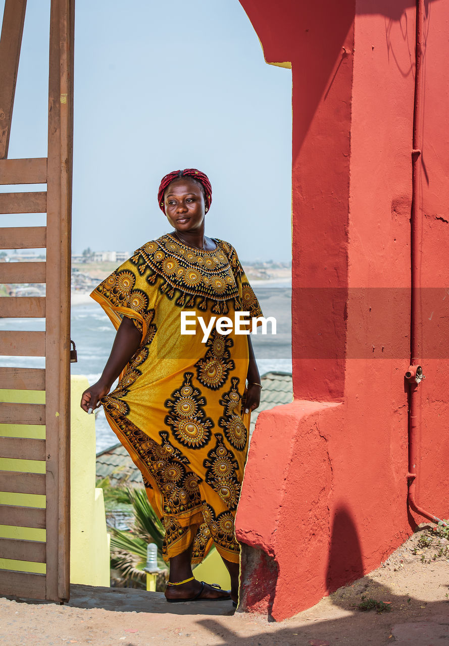 Africa woman wearing yellow suit stands at a gate with background over the city of accra in ghana