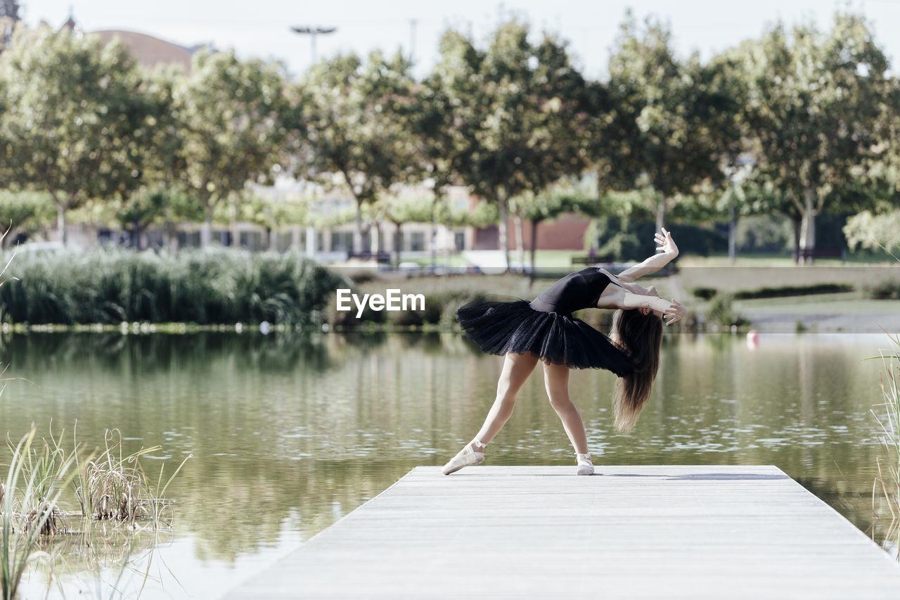Woman Ballet Dancing On Pier Over Lake