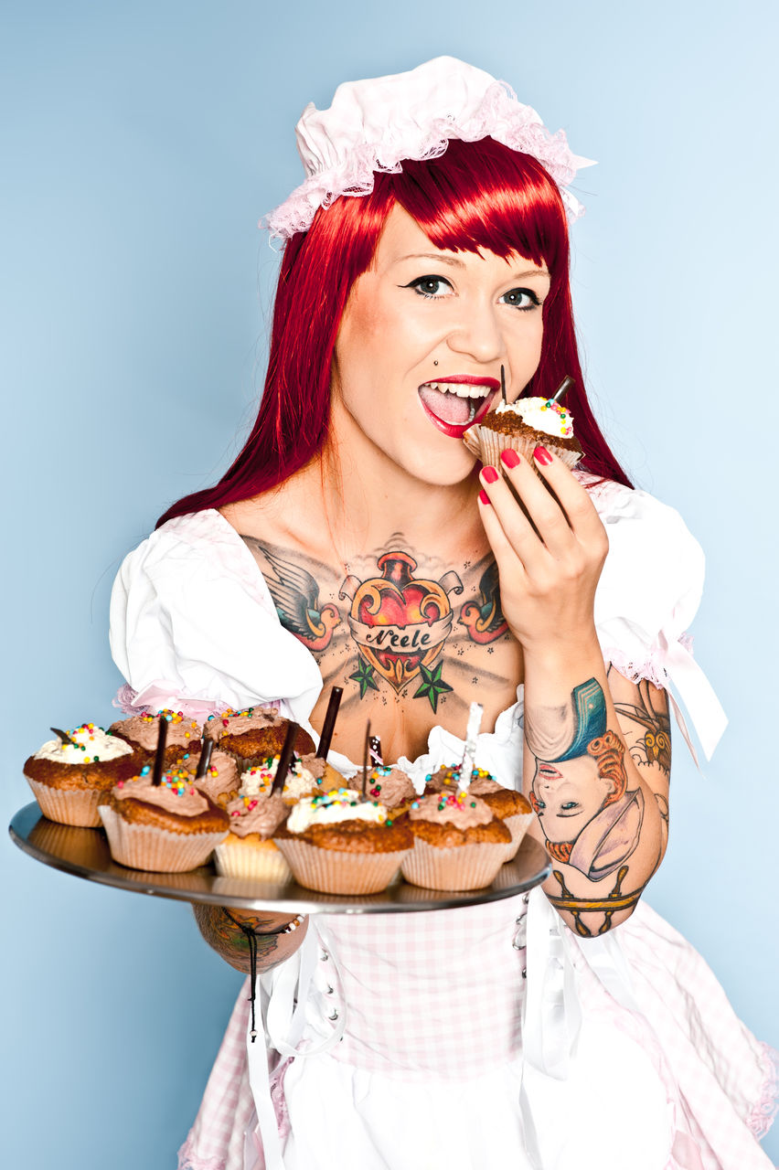 Portrait Of Redhead Woman Having Cupcake Against Blue Background