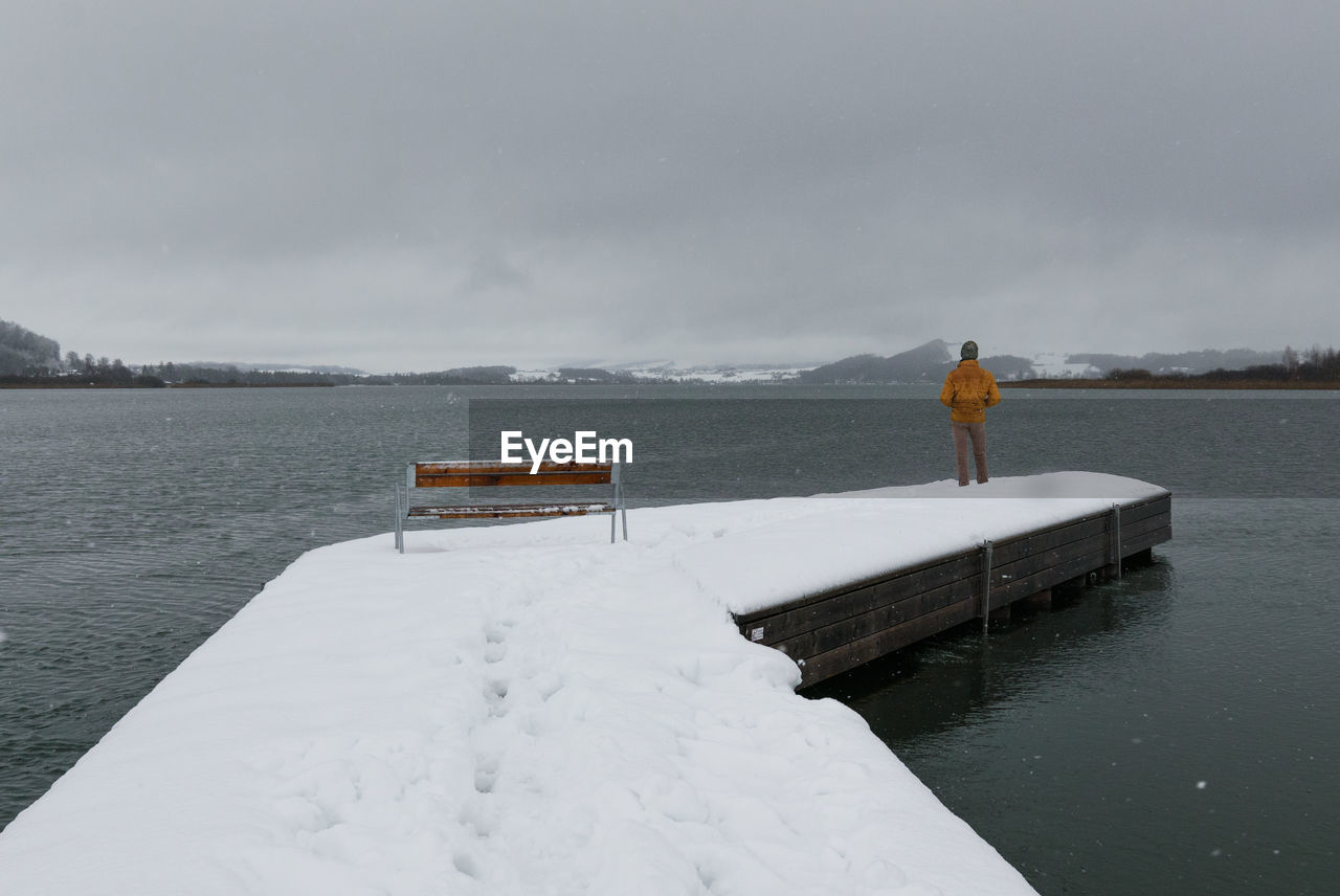 Rear view of man standing at lake against sky during snowfall