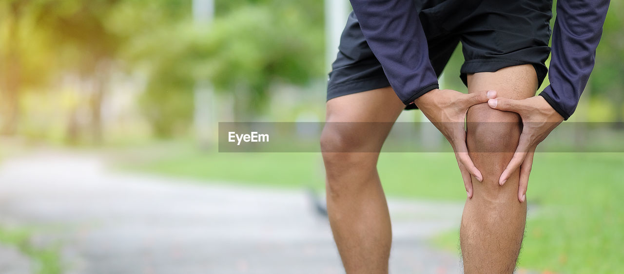Man Touching Knee While Standing On Footpath