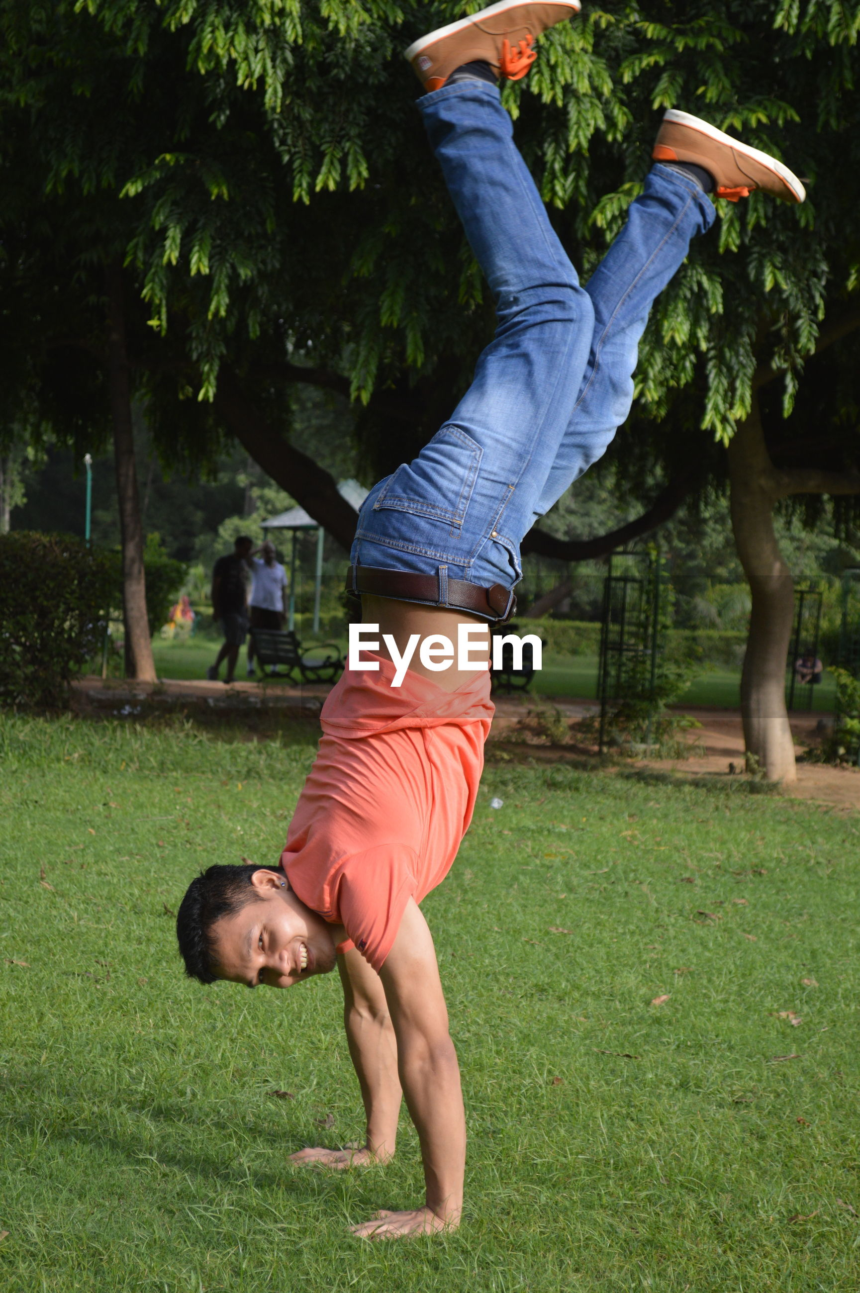 Side view of man doing handstand on grassy field in park