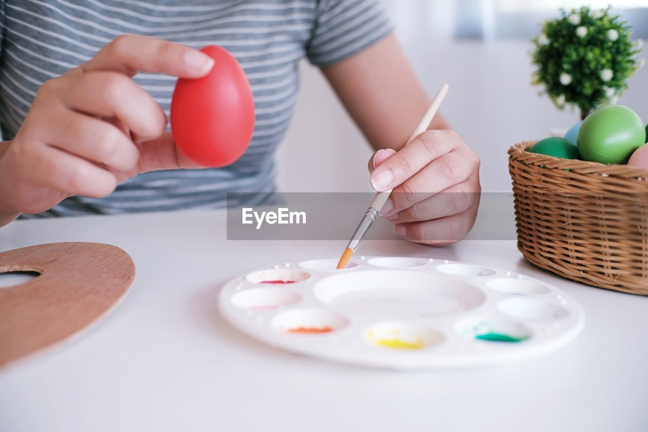 one person, holding, human hand, indoors, midsection, real people, table, food, creativity, hand, food and drink, selective focus, egg, front view, lifestyles, paintbrush, brush, art and craft, adult, table knife