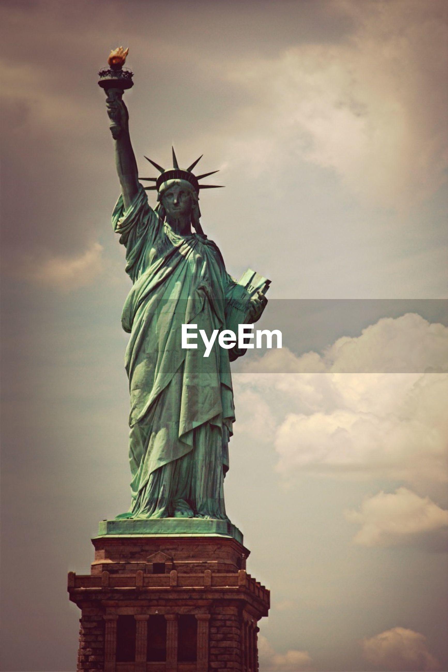 statue, sculpture, human representation, art and craft, art, low angle view, creativity, sky, cloud - sky, travel destinations, travel, animal representation, tourism, famous place, statue of liberty, international landmark, cloudy, outdoors