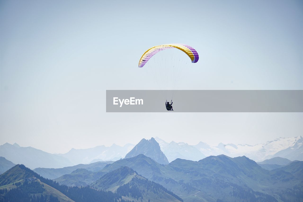 extreme sports, adventure, mountain, parachute, nature, mid-air, real people, paragliding, leisure activity, mountain range, clear sky, flying, day, outdoors, scenics, one person, beauty in nature, low angle view, lifestyles, skydiving, sky, people