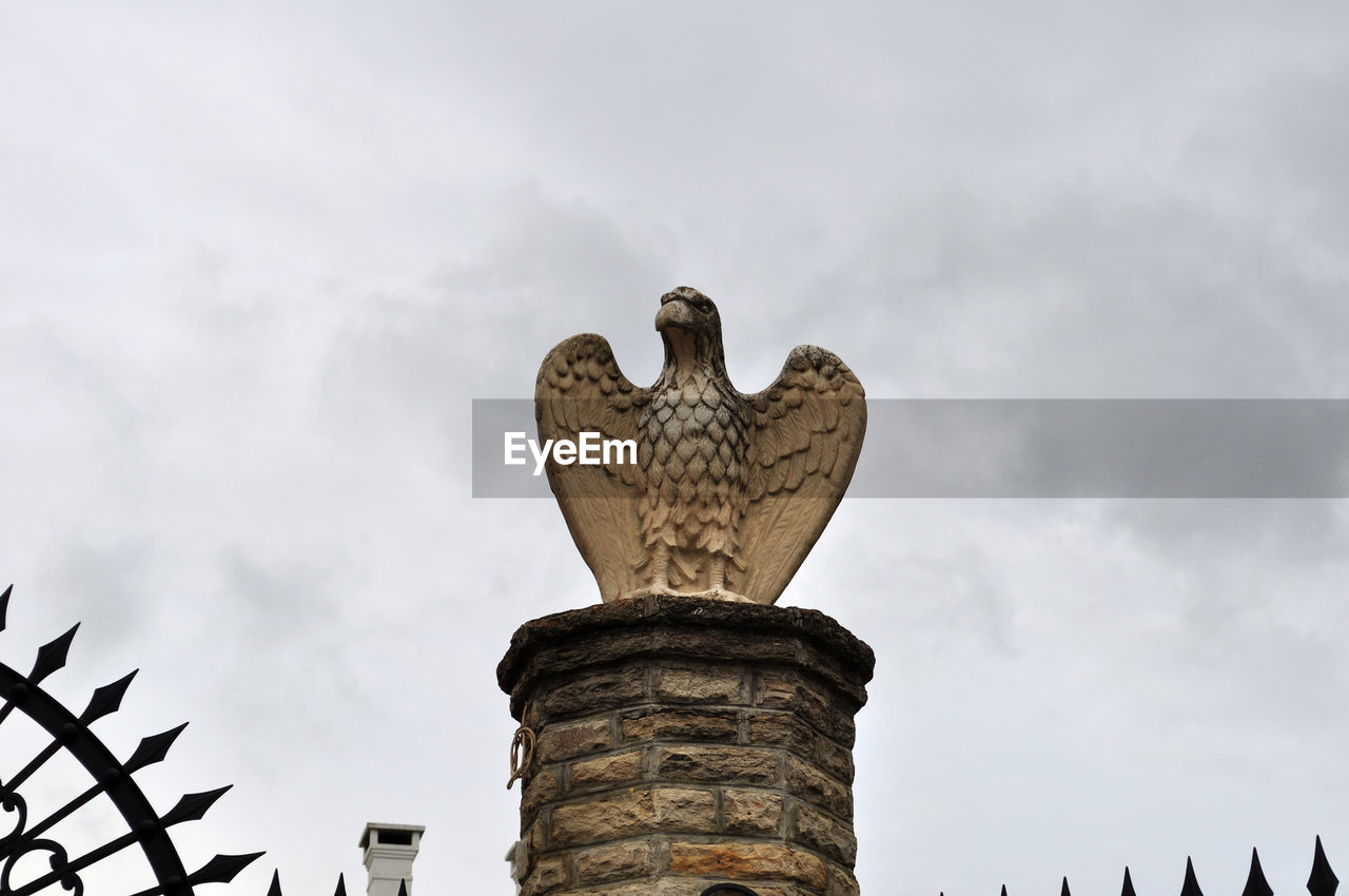 low angle view, sky, cloud - sky, representation, no people, architecture, nature, art and craft, bird, sculpture, animals in the wild, statue, day, vertebrate, creativity, animal wildlife, craft, human representation, outdoors, architectural column, eagle
