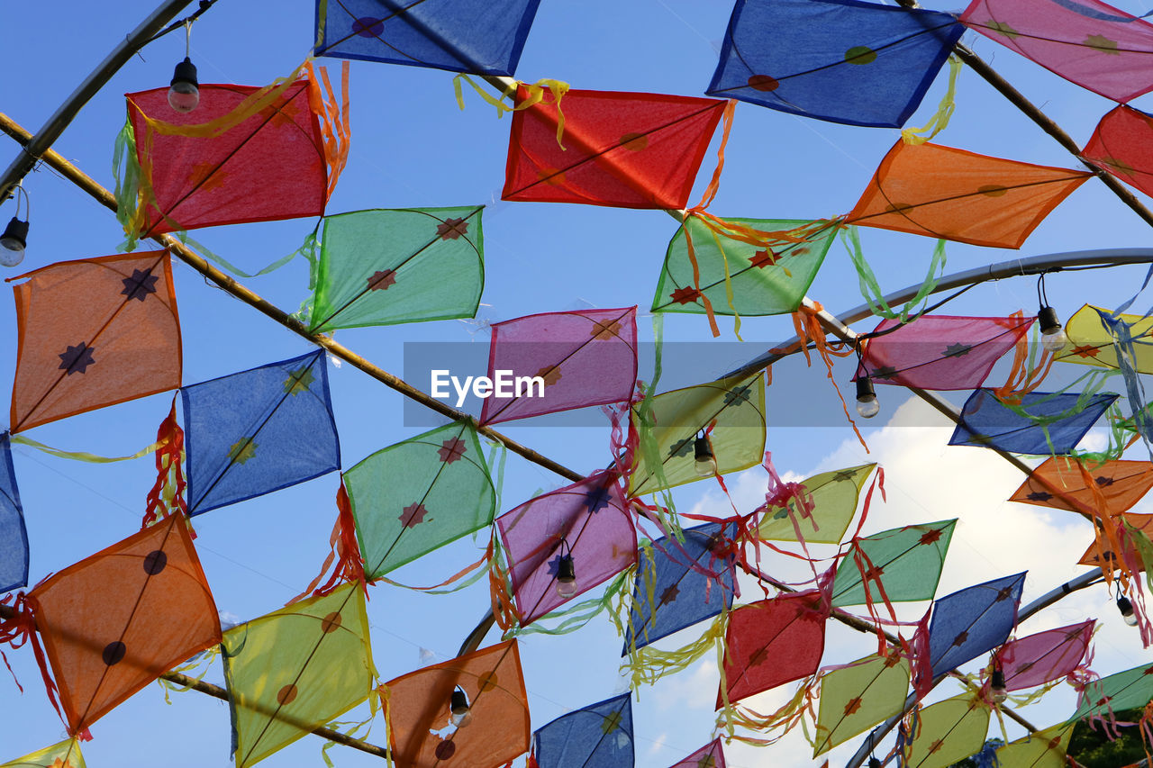 multi colored, sky, low angle view, day, no people, sunlight, hanging, blue, nature, decoration, clear sky, creativity, large group of objects, outdoors, pattern, art and craft, built structure, celebration, triangle shape