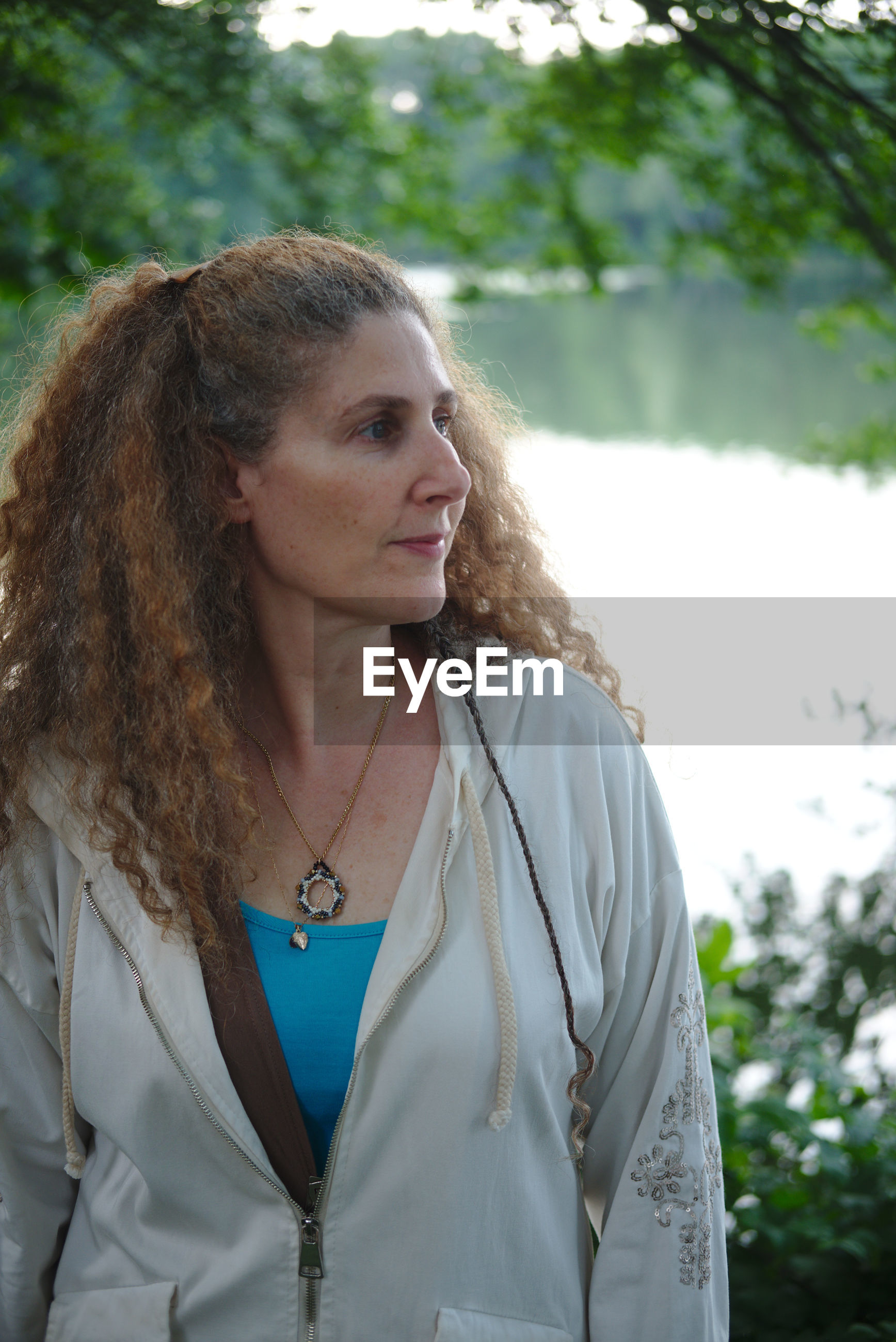 Mature woman looking away while standing against lake