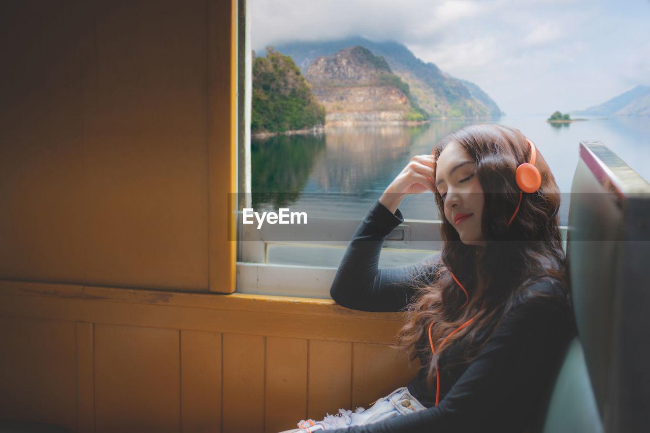 Woman wearing headphone while sitting in train