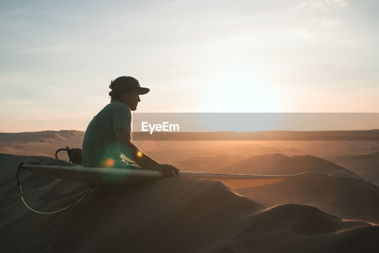sky, sunset, beauty in nature, real people, one person, scenics - nature, lifestyles, leisure activity, men, nature, orange color, land, tranquility, tranquil scene, sunlight, non-urban scene, sun, cloud - sky, idyllic, lens flare, outdoors, arid climate