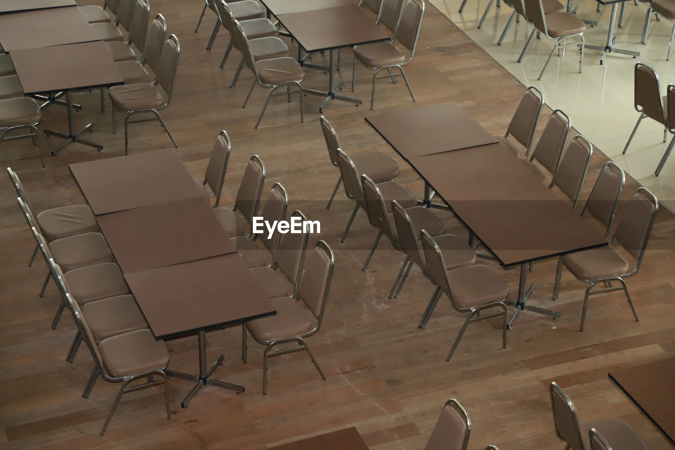 High angle view of empty chairs and tables arranged on hardwood floor