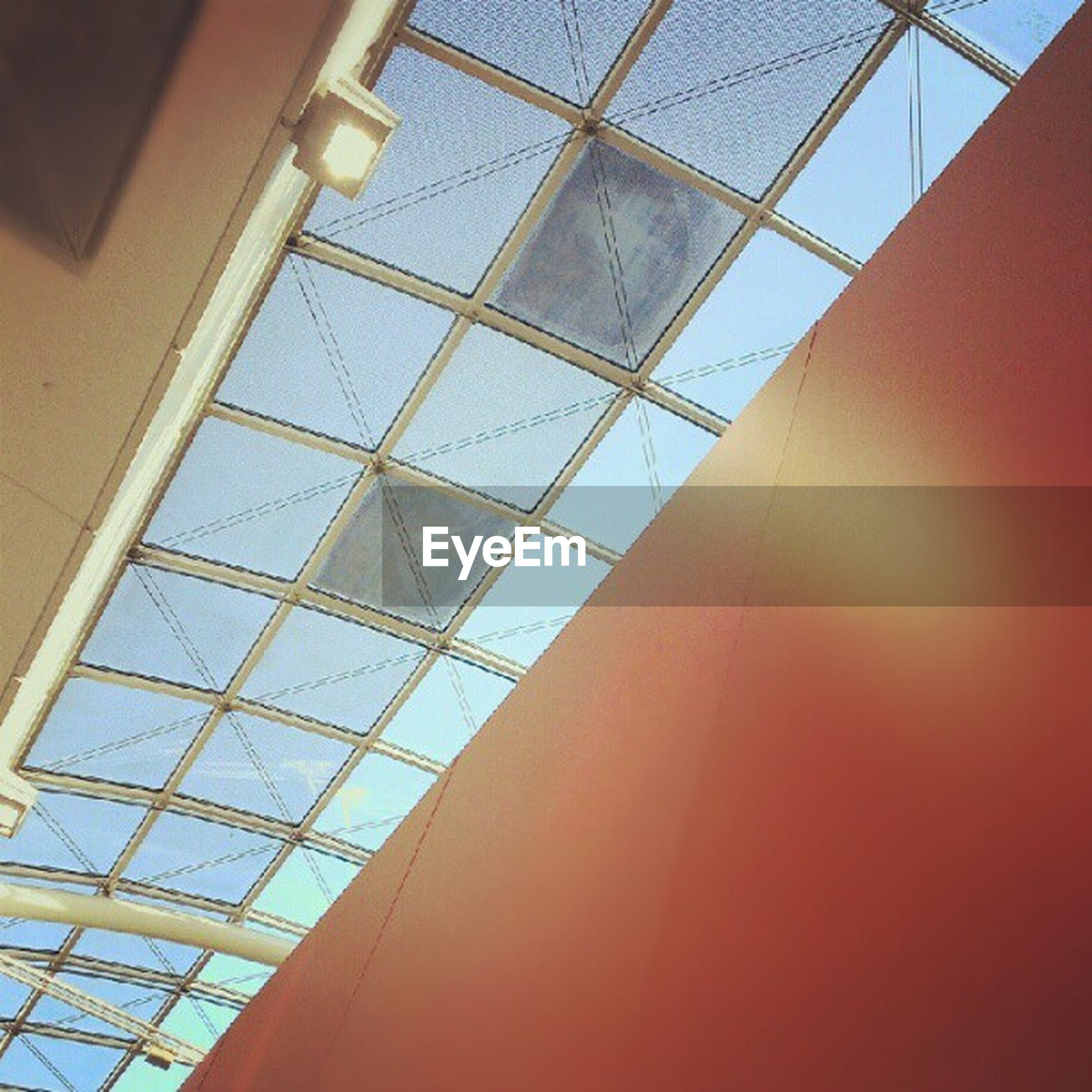 low angle view, indoors, architecture, ceiling, built structure, modern, glass - material, directly below, pattern, architectural feature, skylight, illuminated, geometric shape, design, no people, building, lighting equipment, day, sky, building exterior