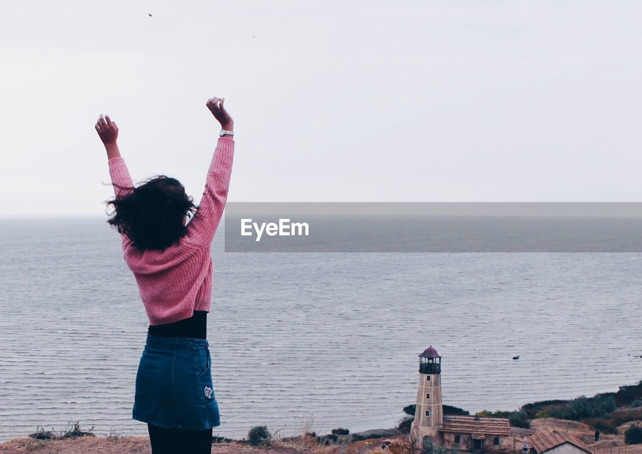 Woman With Arms Raised Standing Against Sea