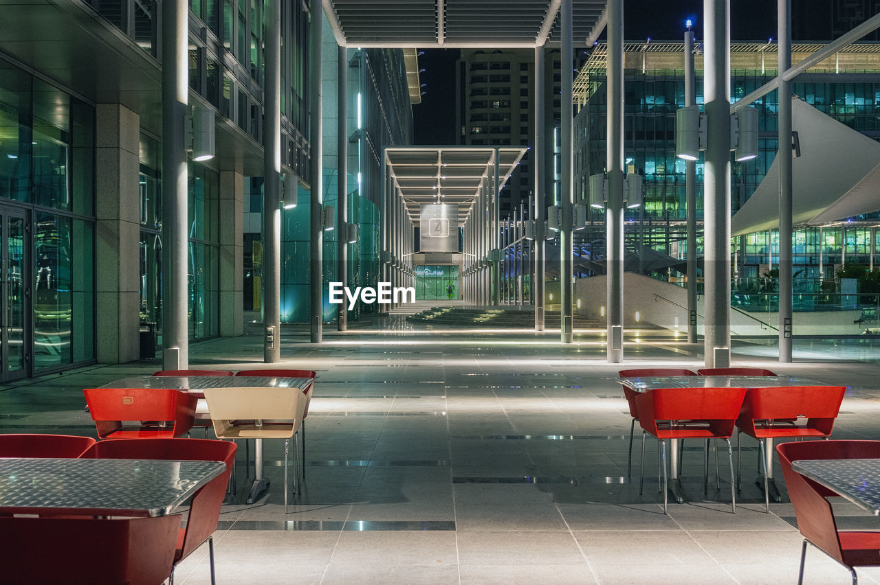 architecture, absence, built structure, seat, building exterior, empty, modern, glass - material, table, no people, chair, business, transparent, building, city, restaurant, outdoors, reflection, illuminated, glass, tiled floor