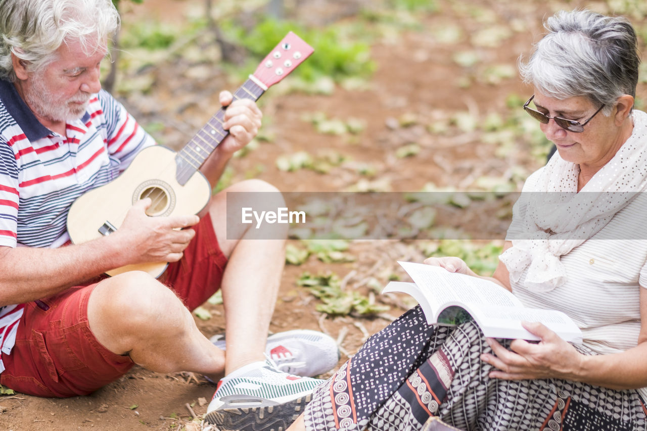 Senior man playing ukulele with woman reading book on field