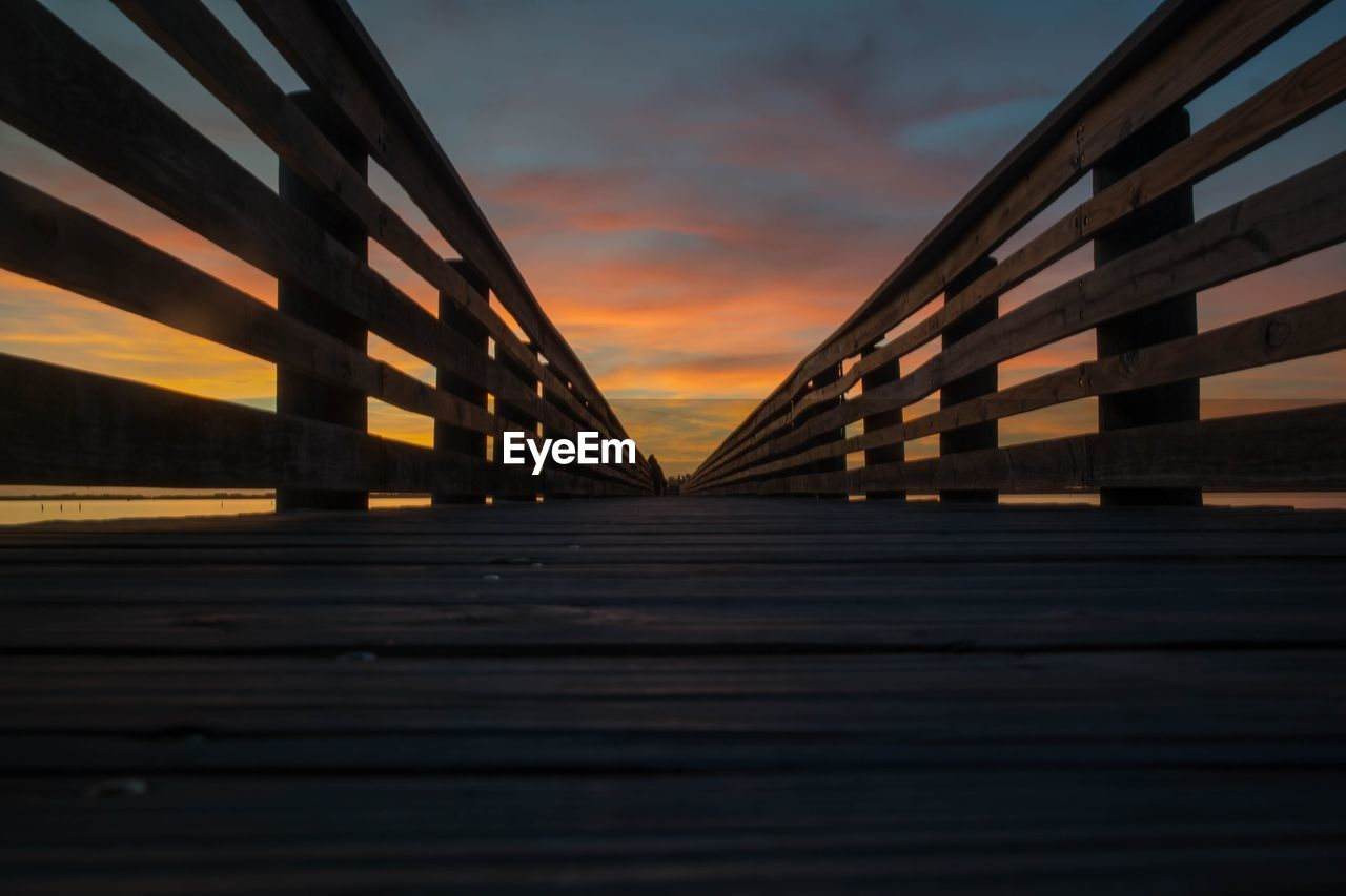 sunset, bridge - man made structure, built structure, connection, sky, architecture, outdoors, no people, wood - material, footbridge, transportation, the way forward, road, nature, water, day, city, close-up