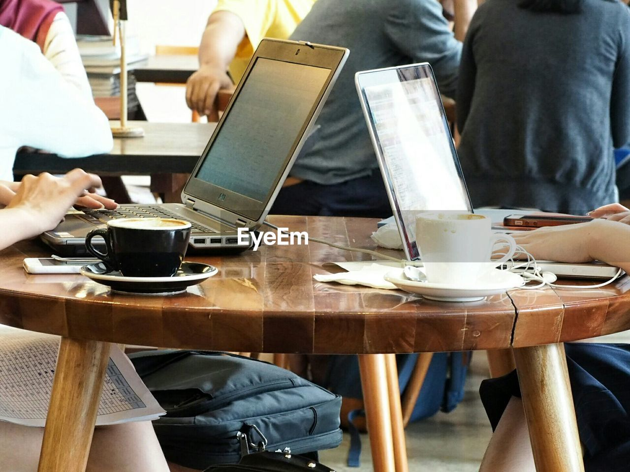 Friends Using Laptop With Coffees At Cafe