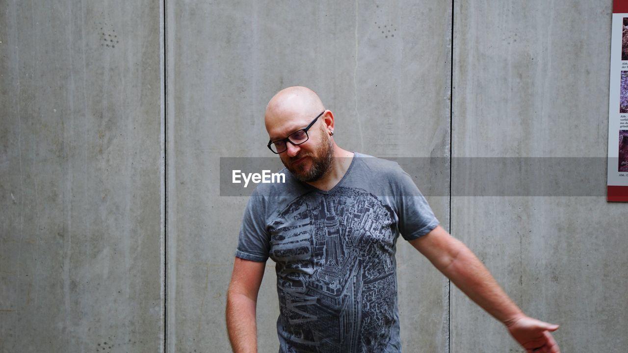 Man Wearing Eyeglasses Against Wall