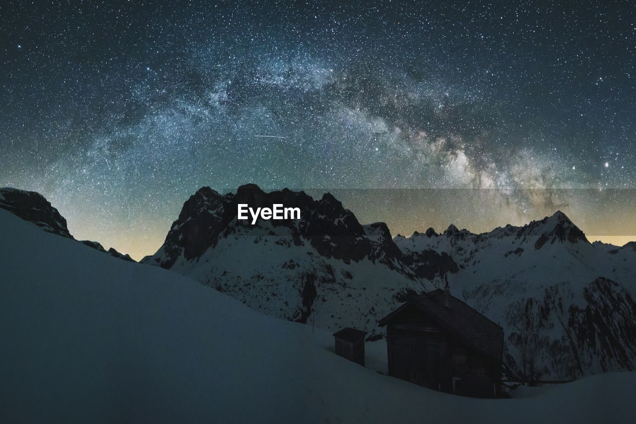 Snow covered landscape against starry sky