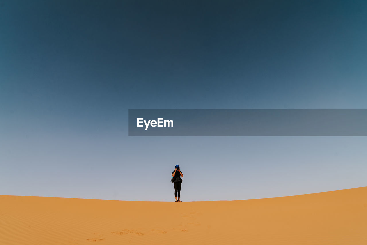 Woman standing on sand dune in desert against clear sky
