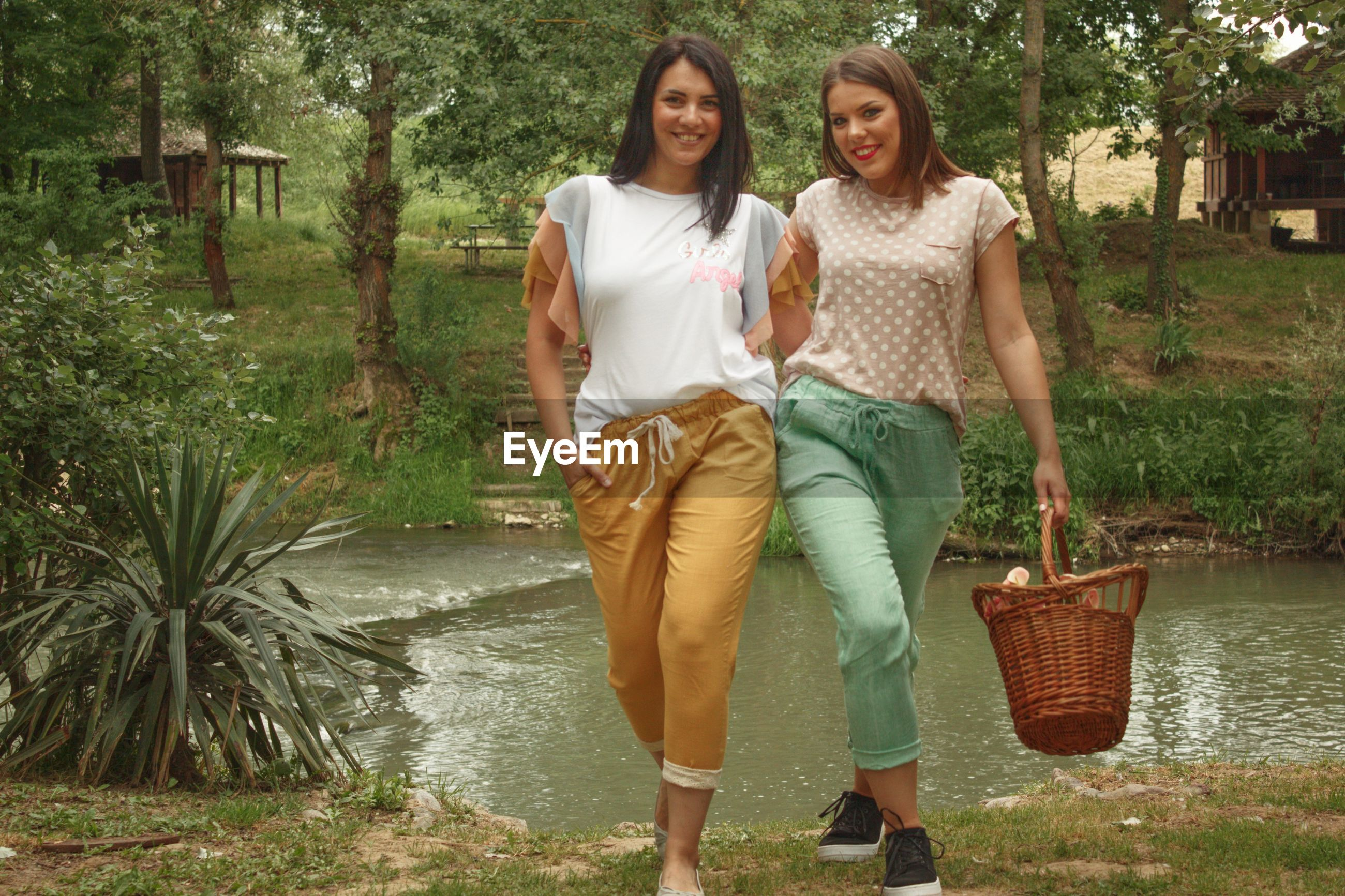 Full length portrait of smiling young women walking by river