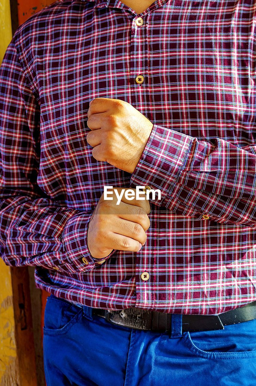 Midsection of man buttoning sleeve