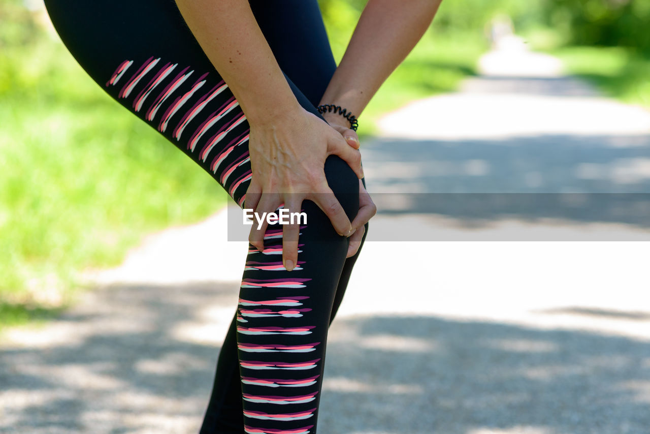 Midsection Of Woman With Leg Pain While Standing On Road