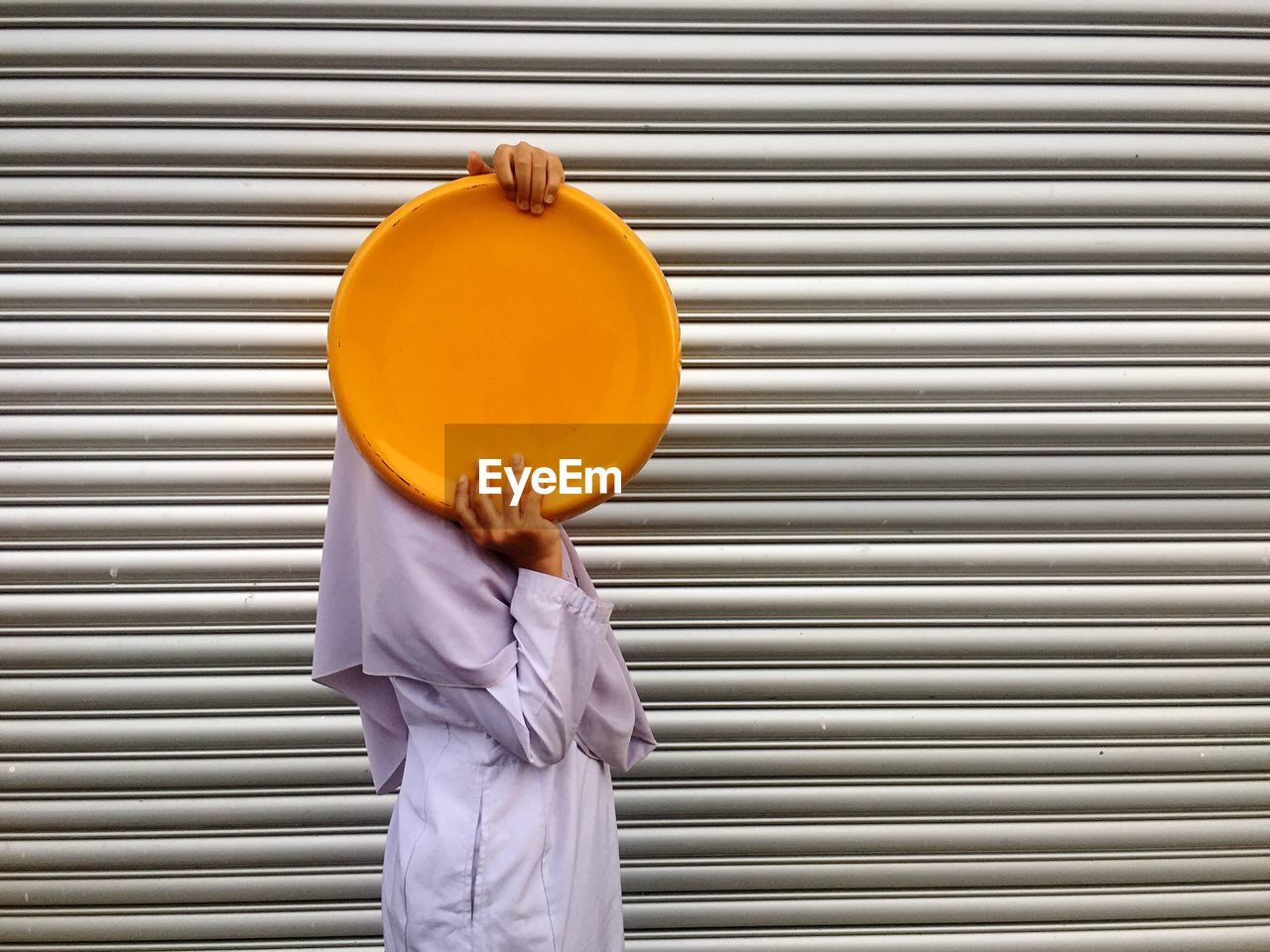 Side View Of Woman Holding Yellow Metal Plate Against Shutter