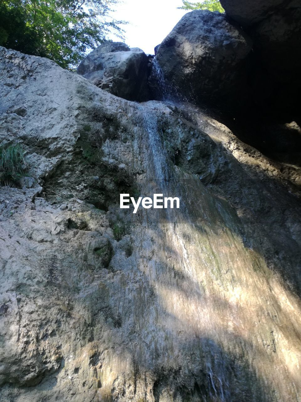 rock - object, nature, rock formation, geology, beauty in nature, low angle view, day, no people, physical geography, outdoors, tranquility, scenics, textured, waterfall, mountain, water, close-up
