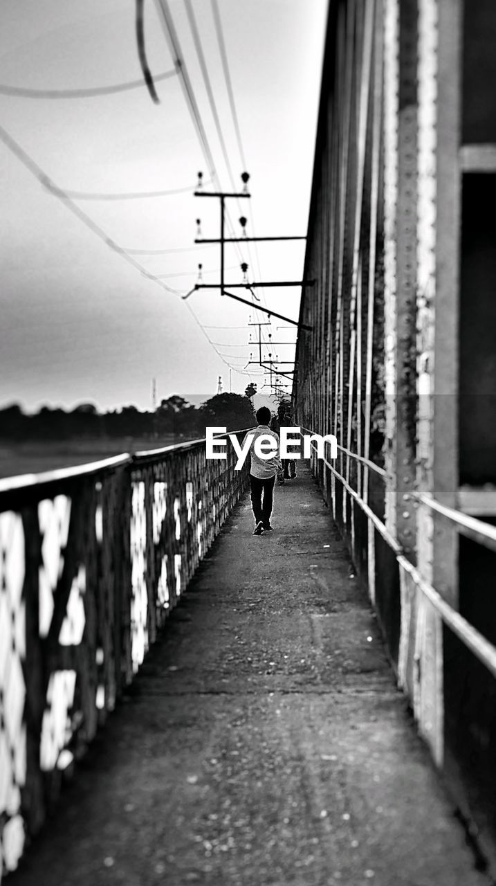 full length, bridge - man made structure, rear view, walking, connection, railing, the way forward, real people, one person, architecture, men, built structure, day, transportation, outdoors, footbridge, sky, one man only, people