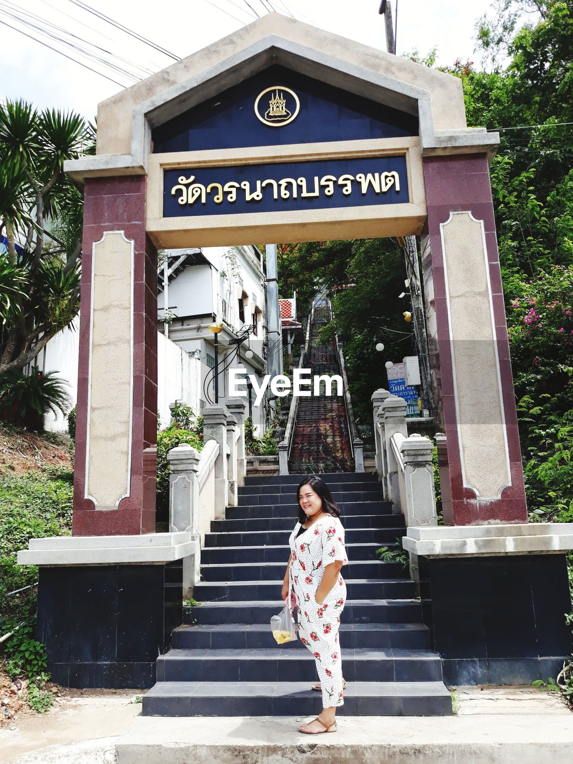 Smiling mid adult woman standing against entrance gate