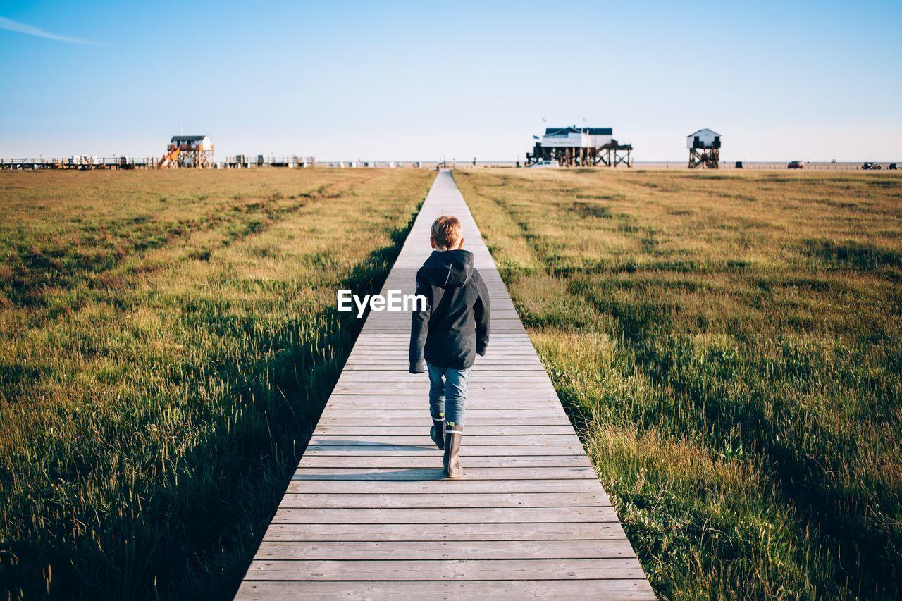 Rear view of boy walking on boardwalk over grassy field