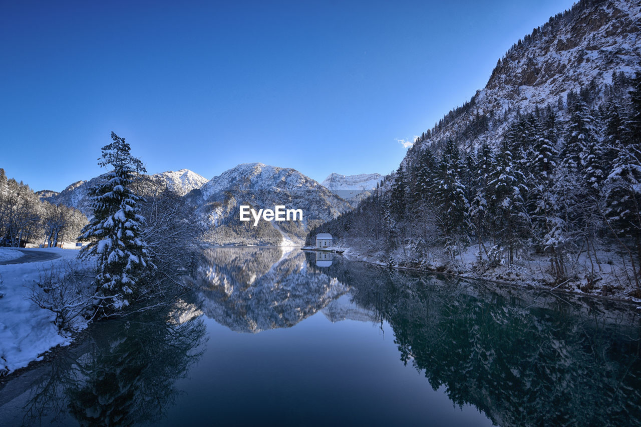 Scenic view of lake by mountains against clear blue sky during winter