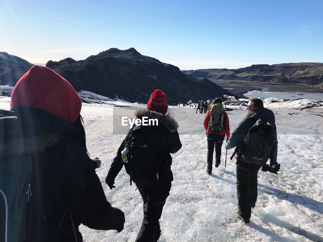 REAR VIEW OF PEOPLE WALKING ON SNOW MOUNTAIN