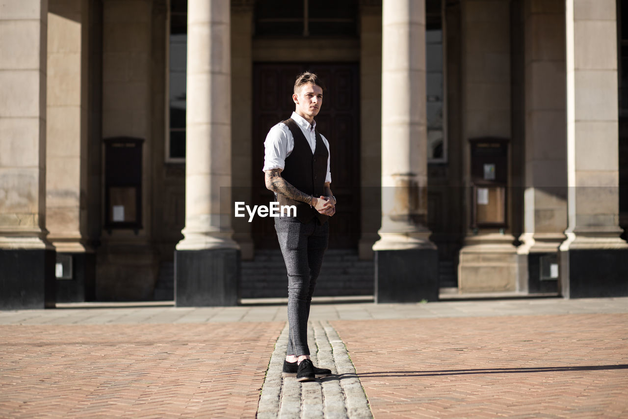 Fashionable man standing on footpath against building