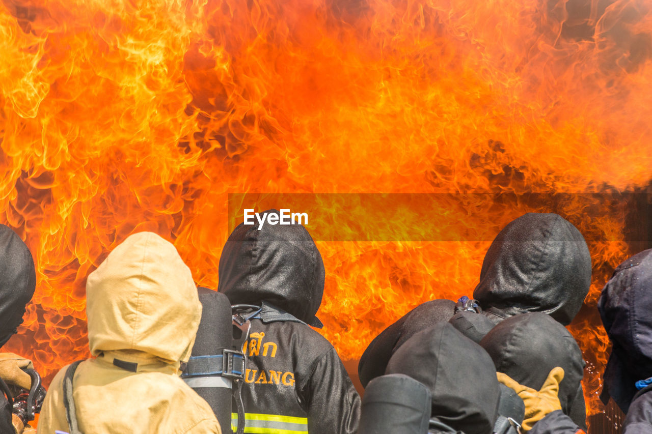 heat - temperature, burning, fire, fire - natural phenomenon, flame, people, rear view, orange color, day, group of people, architecture, real people, nature, clothing, adult, outdoors, headshot, accidents and disasters, waist up, sign