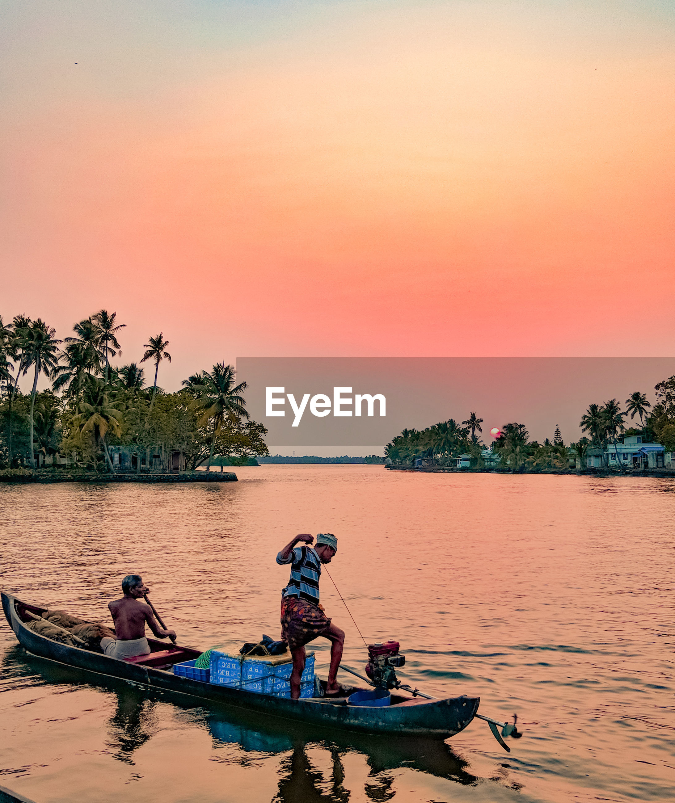 Fishermen in boat on lake against clear sky during sunset