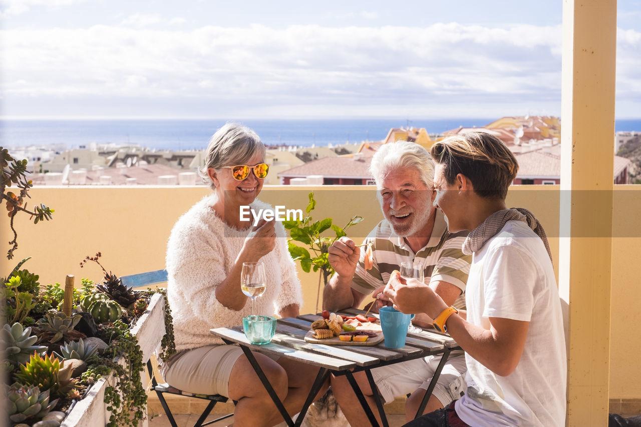 Happy Family Enjoying Food At Outdoors Restaurant