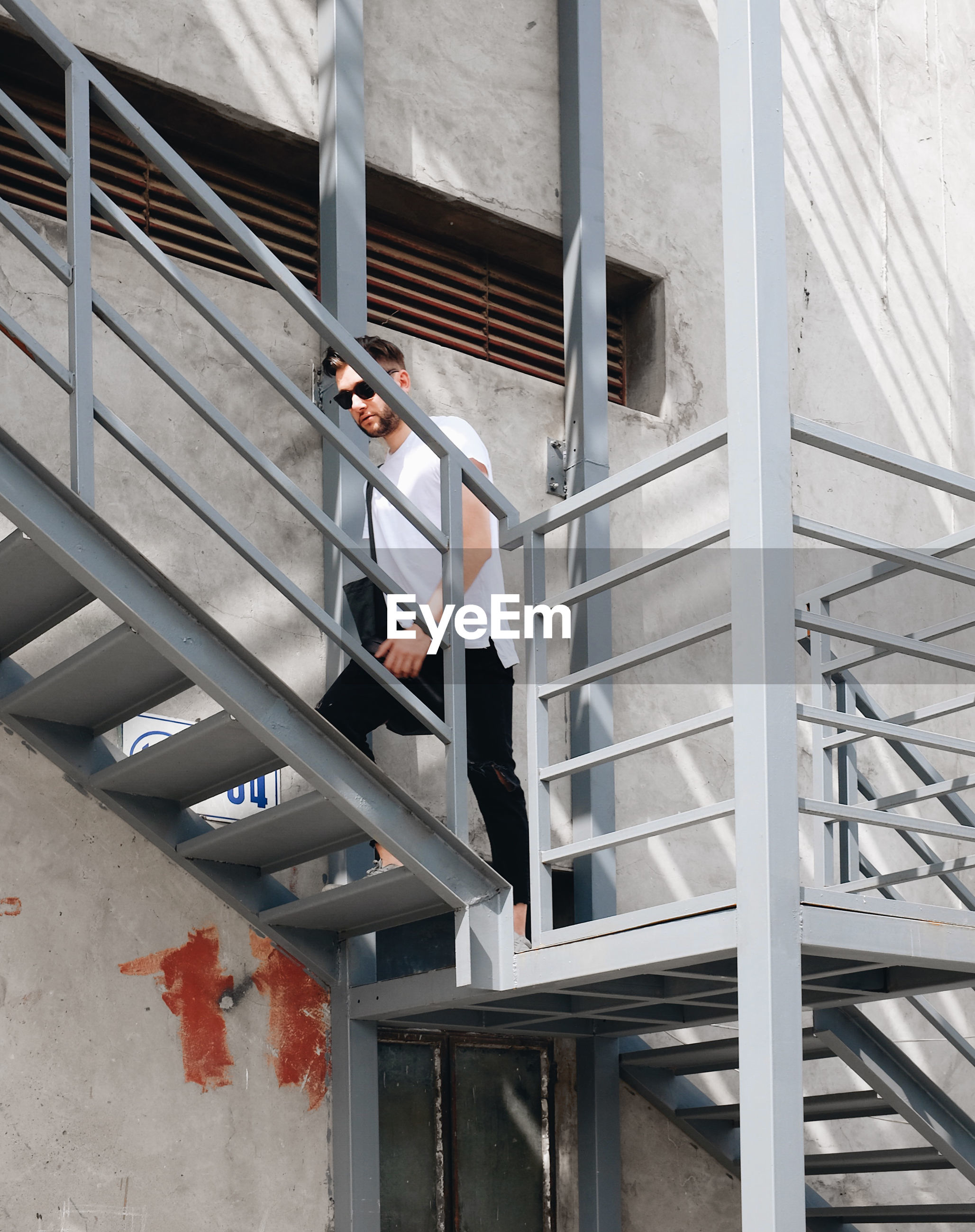 Low angle view of young man moving up on steps