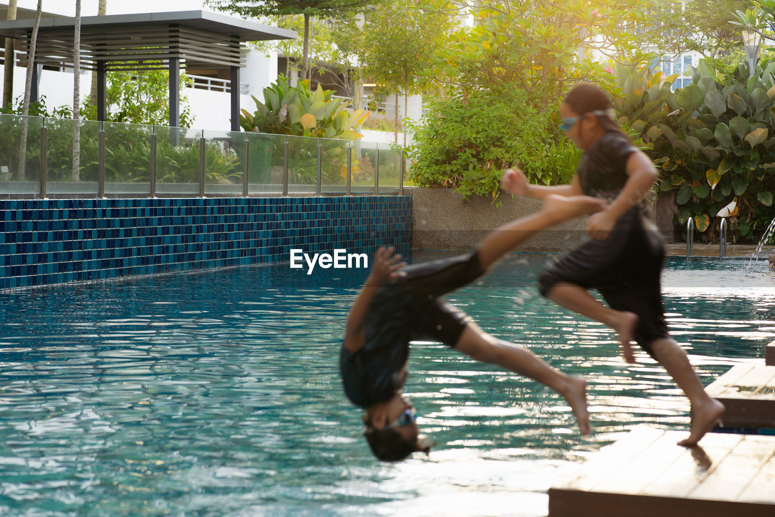 MAN JUMPING IN SWIMMING POOL AGAINST TREES