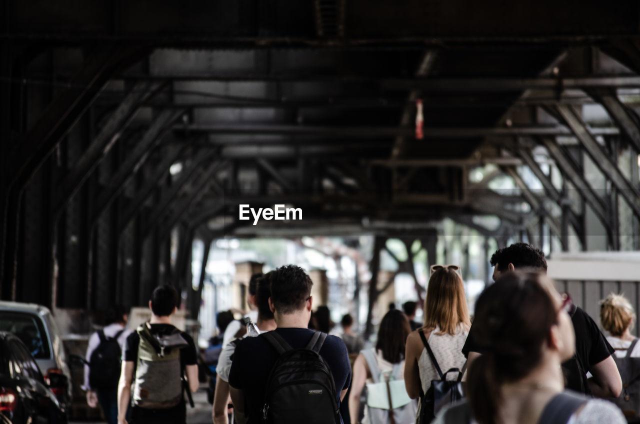 Rear view of people walking in covered bridge
