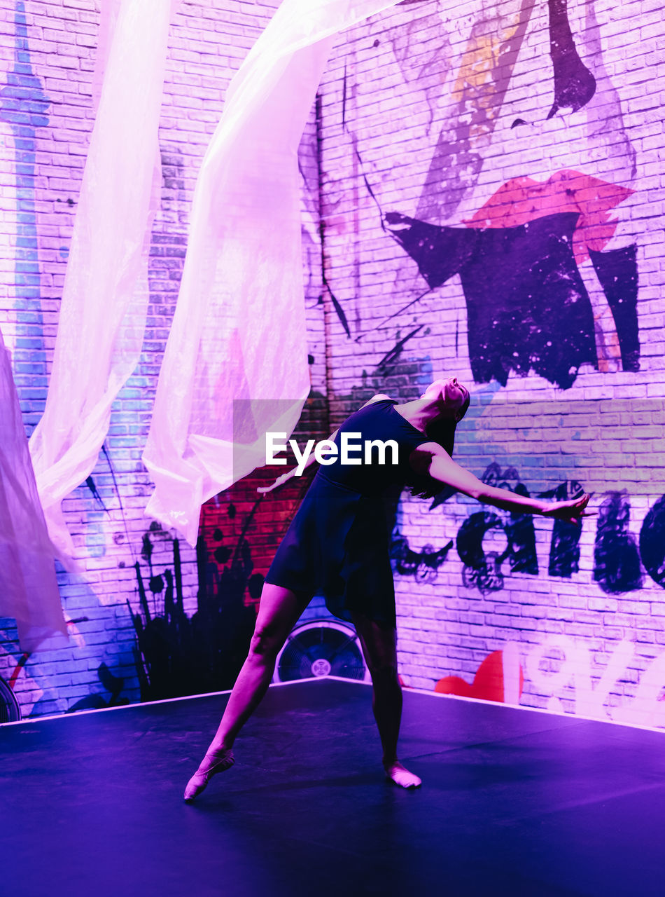 full length, one person, real people, dancing, lifestyles, arts culture and entertainment, skill, performance, leisure activity, stage, stage - performance space, indoors, women, adult, balance, standing, sport, casual clothing, females