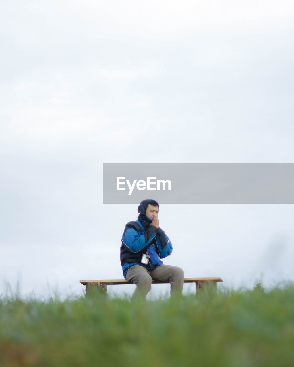 Young man sitting on bench against sky