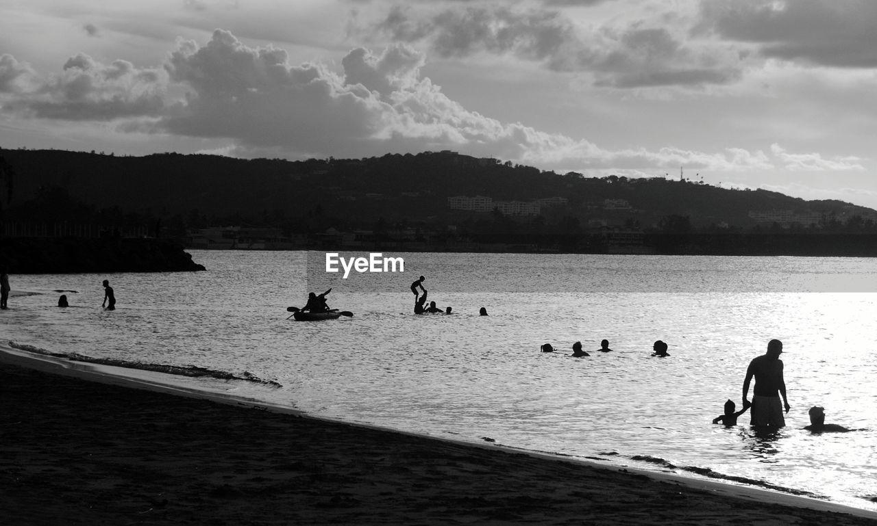 Silhouette People Enjoying At Beach Against Sky